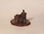 Snapshot of Lincoln Seated at Table Statuette